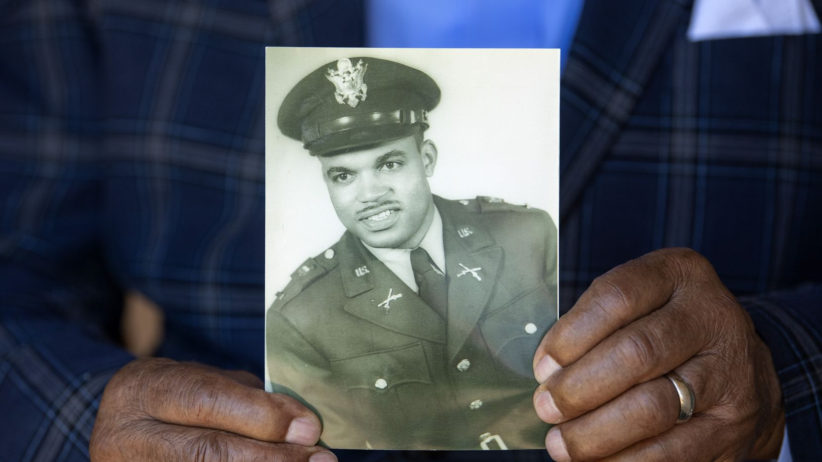 Ezell Holley, 90, holds a 1953 photo taken when he was a second lieutenant in the Army.