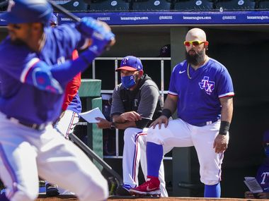 Texas Rangers infielder Rougned Odor (right) watches in the dugout with manager Chris Woodward as outfielder Leody Taveras bats during the third inning of a spring training game against the Cleveland Indians at Surprise Stadium on Tuesday, March 9, 2021, in Surprise, Ariz.