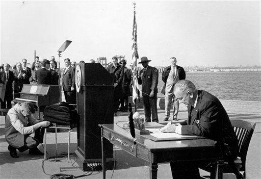 Lyndon B. Johnson firma ley migratoria  de 1965 en Liberty Island. AP