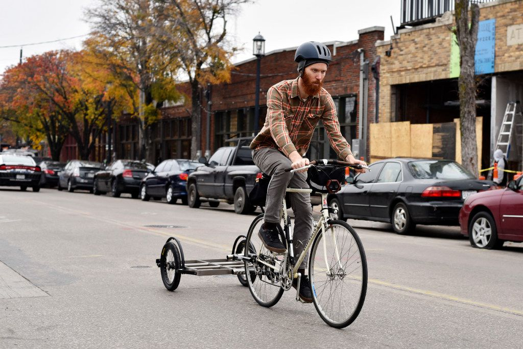 Mark Draz, 29, a library associate at the downtown Dallas branch, rides a prototype model of the book bike attached with a trailer in Deep Ellum. The Dallas Public Library and Local Hub Bicycle Co. are partnering to create a bookbike, a bike that transports a small mobile library to the community.