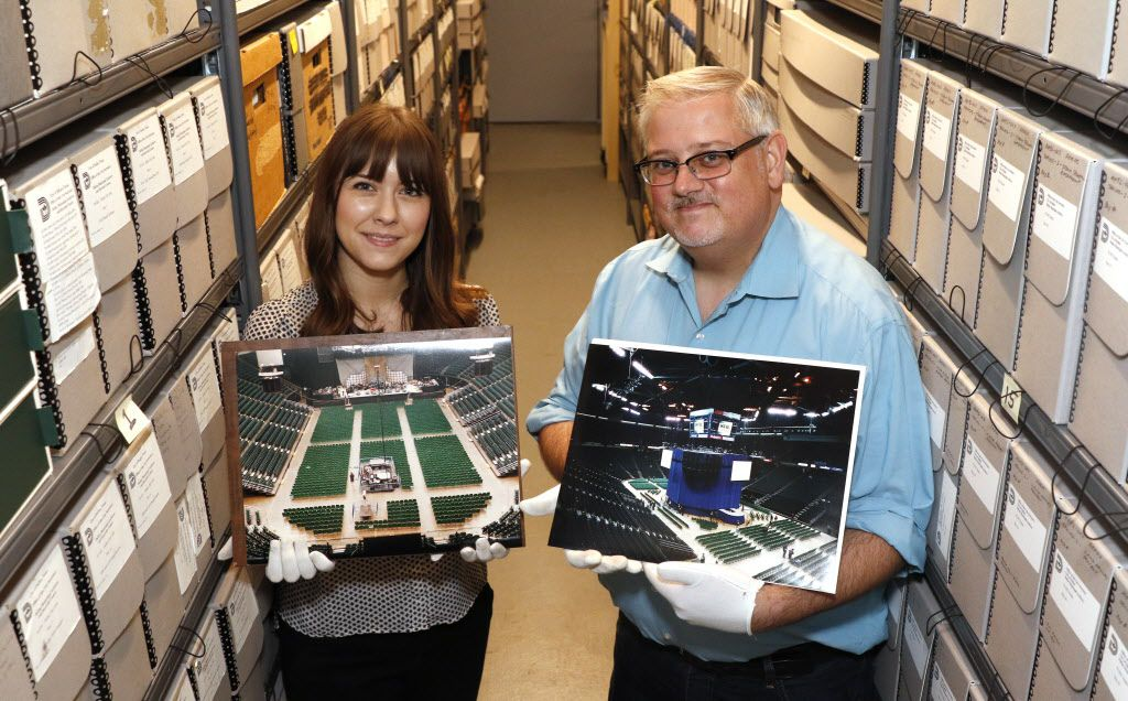 Kelley Smith, archivist volunteer, left, and John Slate, City of Dallas Archivist, hold old photographs of different seating set ups for concerts at Reunion Arena in the archives office in Dallas City Hall on Monday, July 27, 2015 in Dallas.