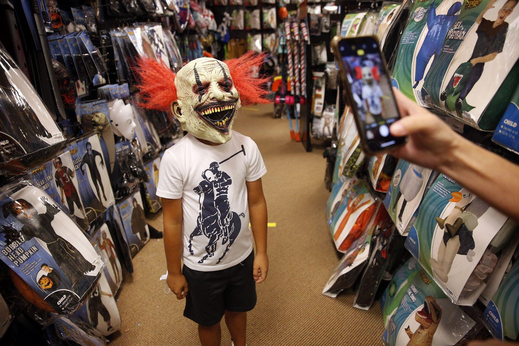 Carey Marin of Richardson takes a photo of her son, Joshua, wearing a clown mask at Spirit Halloween.