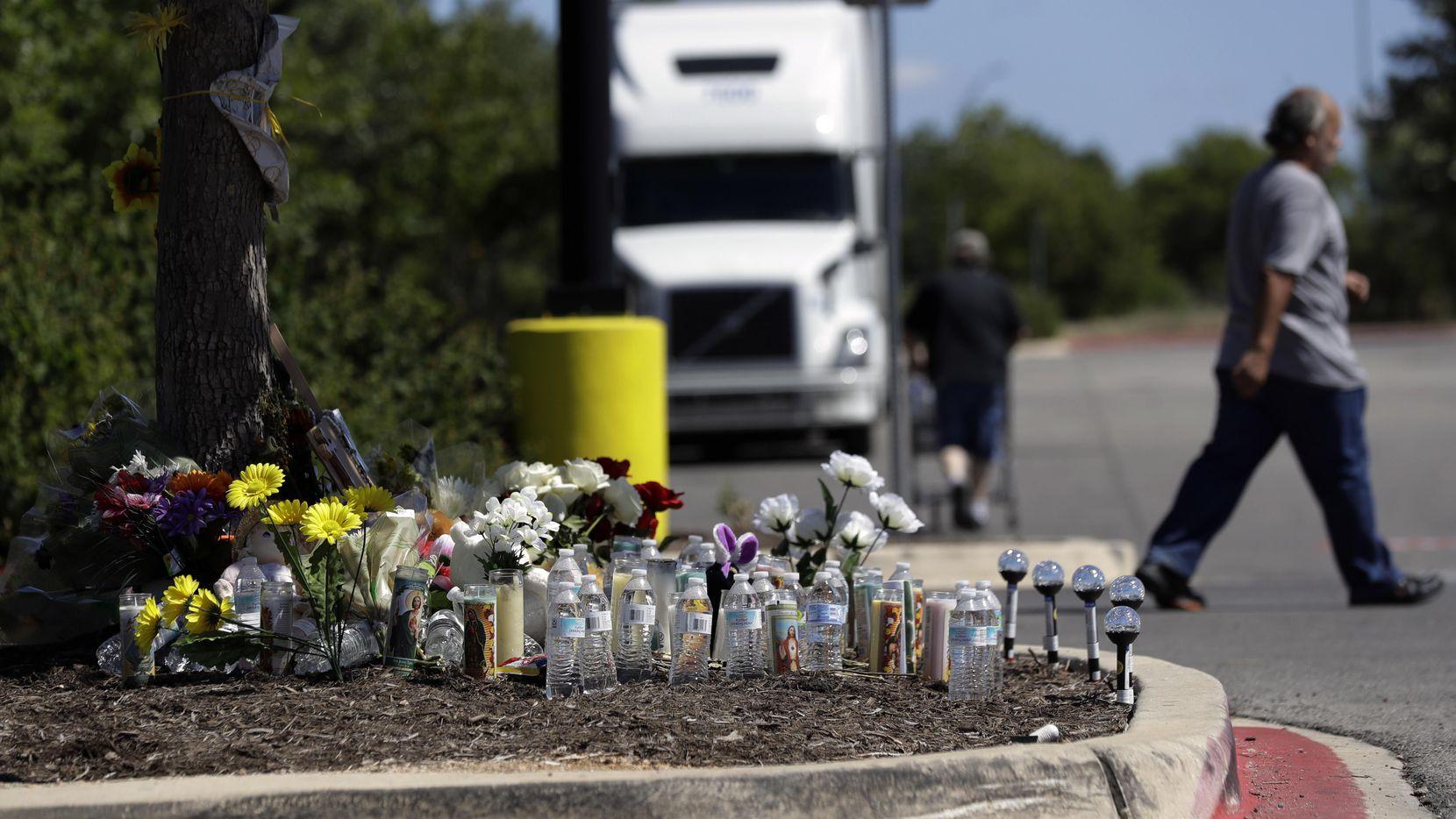 Un hombre deja una veladora en un altar en el lugar donde se encontraron a decenas de inmigrantes encerrados en un remolque de trailer. AP(AP)
