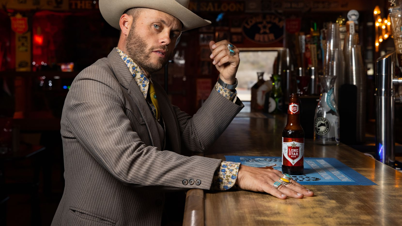 Charley Crockett poses Tuesday at the bar of the Little Longhorn Saloon in Austin, where he first saw James Hand perform.