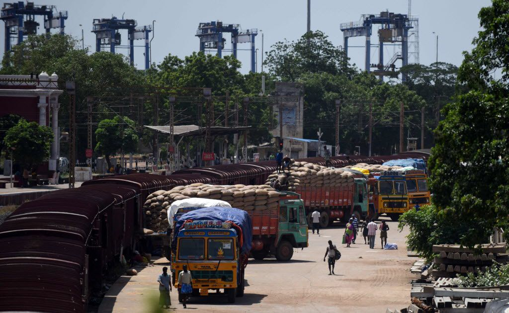 An Indian labourer loads grain sakcs on to a truck at a railway goods yard in Chennai on August 3, 2016.