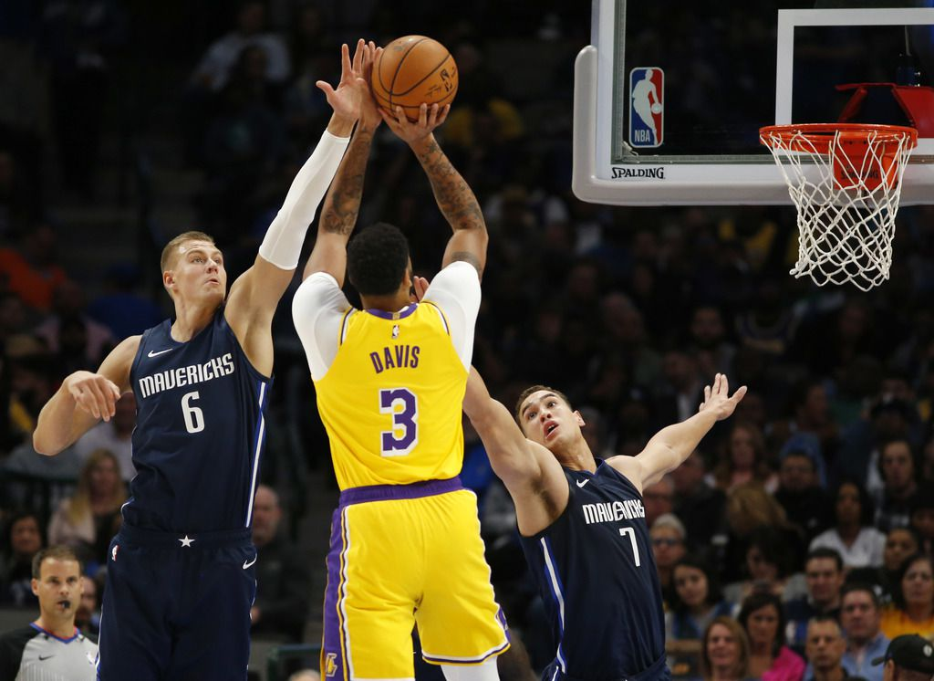 Los Angeles Lakers forward Anthony Davis (3) shoots as Dallas Mavericks forward Kristaps Porzingis (6) and Dallas Mavericks forward Dwight Powell (7) defend during the first quarter of play at American Airlines Center in Dallas on Friday, November 1, 2019. (Vernon Bryant/The Dallas Morning News)