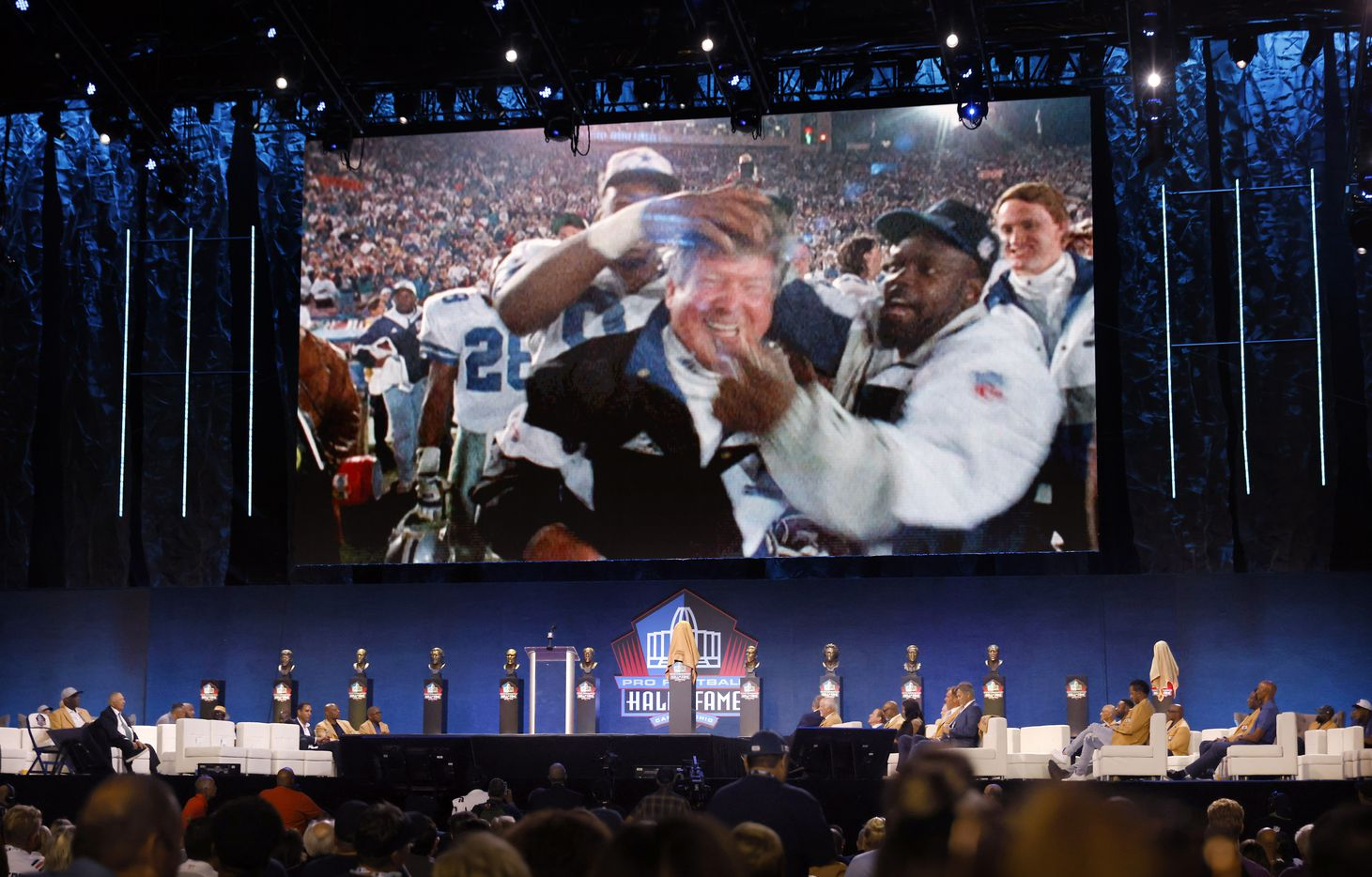 Photos of Pro Football Hall of Fame inductee Jimmy Johnson of the Dallas Cowboys celebrating their Super Bowl win is shown on the video board during the Centennial Class of 2020 enshrinement ceremony at Tom Benson Hall of Fame Stadium in Canton, Ohio, Saturday, August 7, 2021. (Tom Fox/The Dallas Morning News)