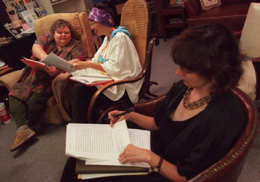 In 2000, Thea Temple (right), executive director of The Writer's Garret, read  a participant's short fiction while other participants, Linda Tiner (left), of Garland, and Azure Ortega (center), of Dallas,  looked over critiques during a Writer's Garret meeting held upstairs at Paperbacks Plus in Dallas.
