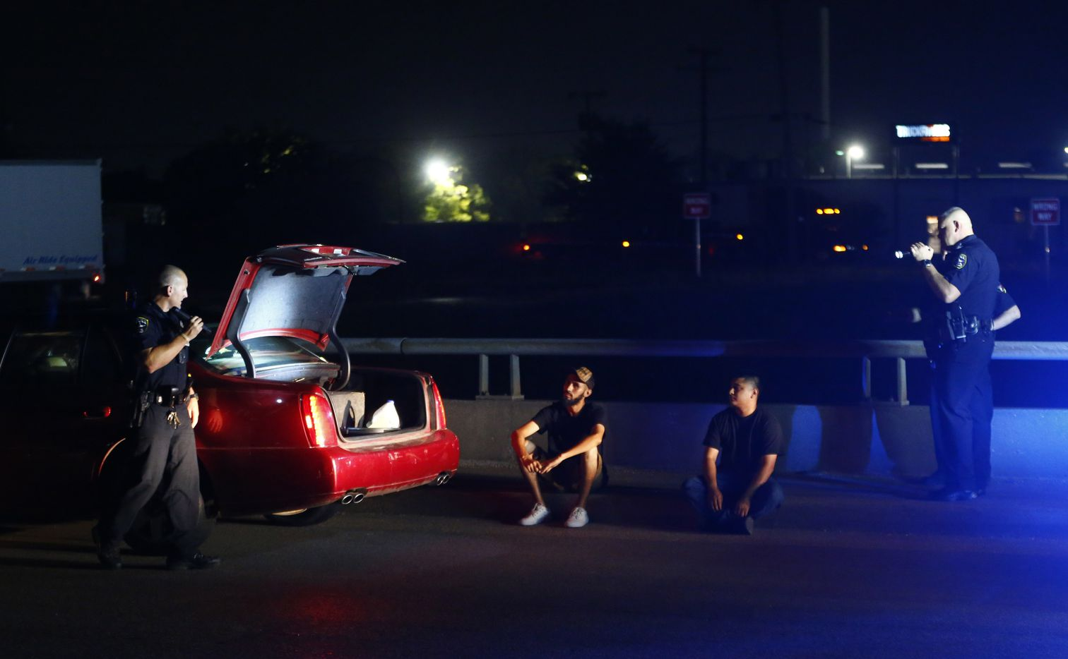 DWI unit officers Allen Lotspeich (left) and Stephen Burres talk to a suspected drunk driver and his passenger in Irving on July 21.  The two were let go with a citation for an open container in the car.