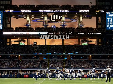 FILE - The sunset is seen through the open end zone doors at AT&T Stadium as the Dallas Cowboys run a second-half play against the Los Angeles Rams in Arlington on Sunday, Dec. 15, 2019.