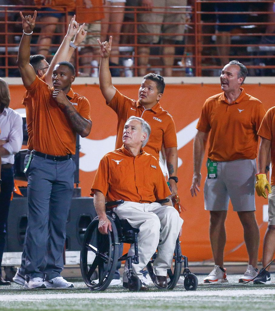 Texas Governor Greg Abbott, seated center, watches the third quarter of a college football game between the University of Texas and Louisiana State University on Saturday, Sept. 7, 2019 at Darrell Royal Memorial Stadium in Austin, Texas. (Ryan Michalesko/The Dallas Morning News)