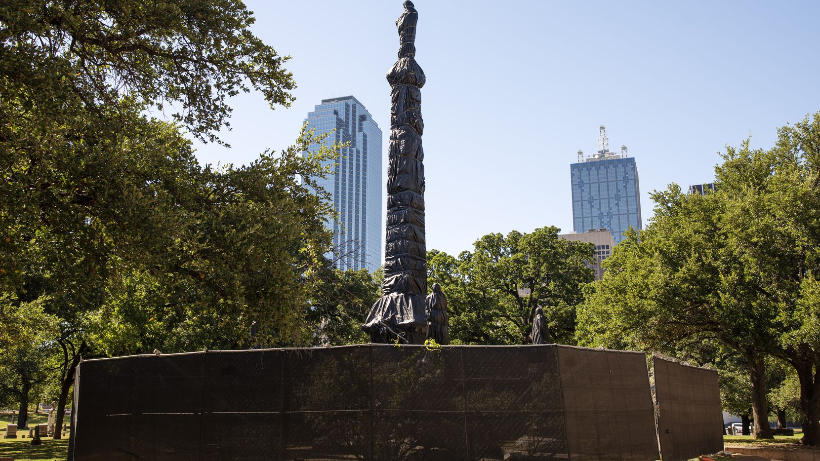 The statues and monument of the Confederate War Memorial are fenced in and wrapped with black plastic, near the Kay Bailey Hutchison convention center and Pioneer Park Cemetery in downtown Dallas, Thursday, June 11, 2020.