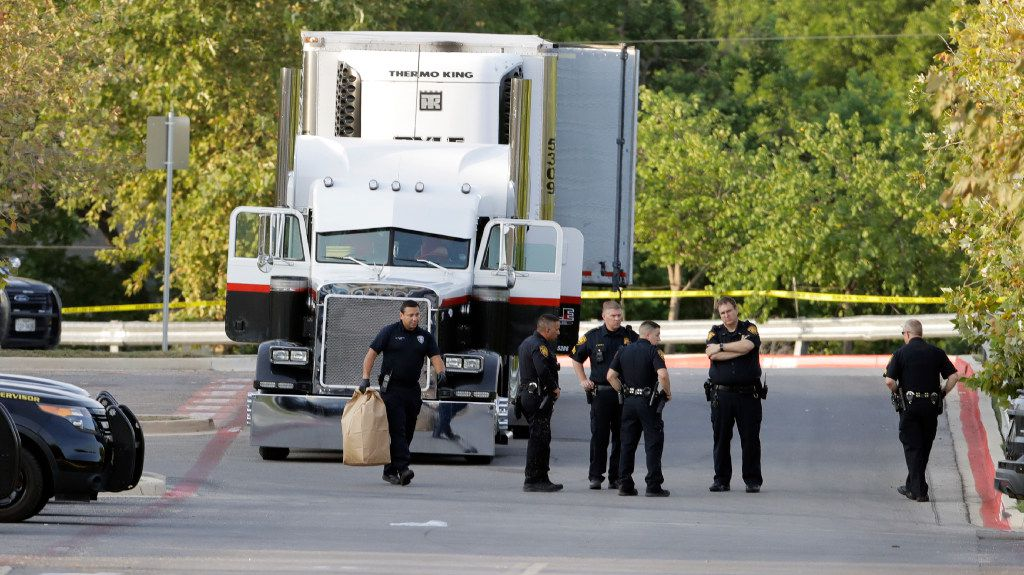 San Antonio police officers investigate the scene Sunday, July 23, 2017, where eight people were found dead in a tractor-trailer loaded with at least 30 others outside a Walmart store in stifling summer heat in what police are calling a horrific human smuggling case,  in San Antonio.