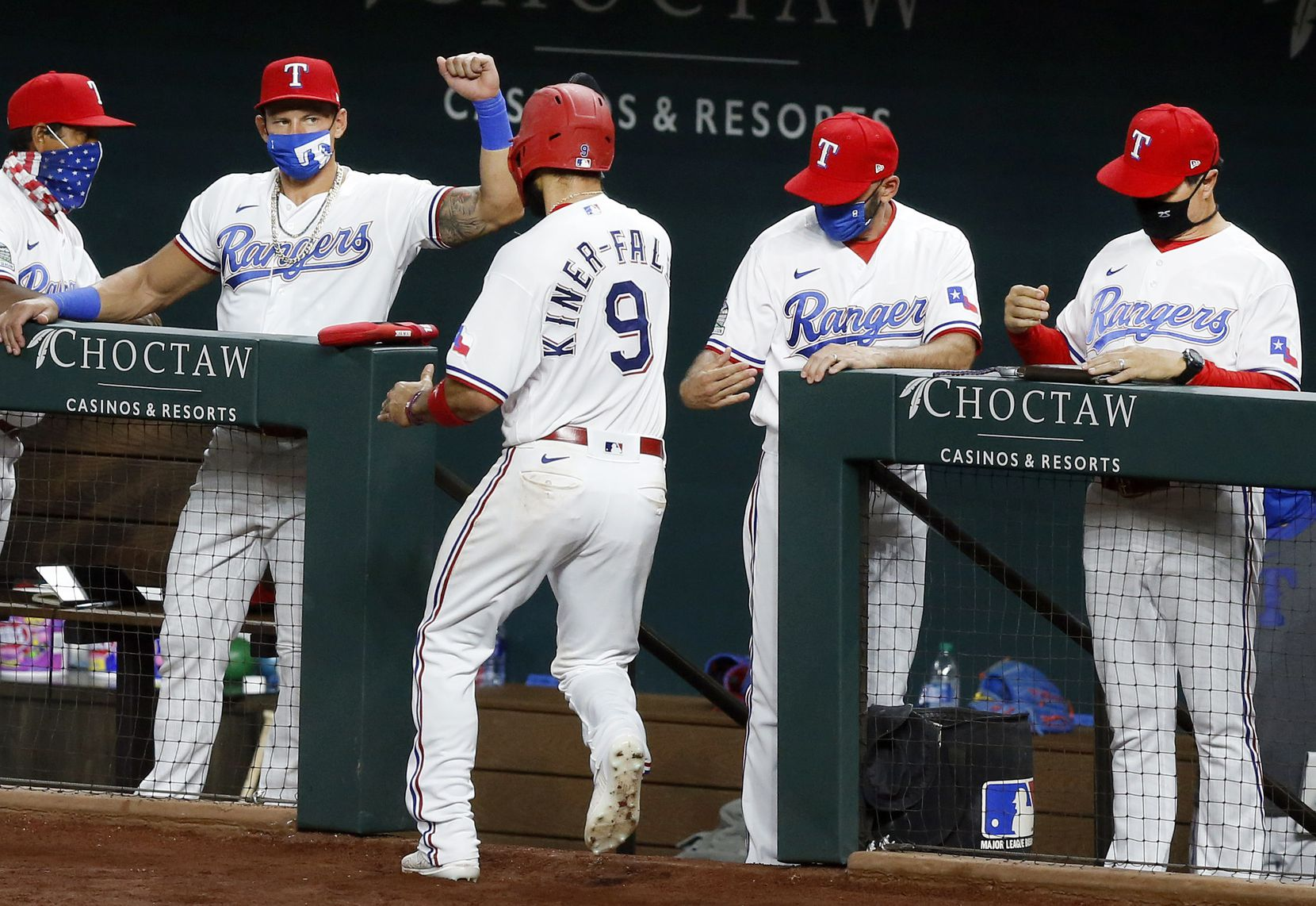 Texas Rangers Isiah Kiner-Falefa (9) is congratulated by the coaching staff and players after he scored on a Nick Solak single in the third inning against the Seattle Mariners at Globe Life Field in Arlington, Tuesday, August 11, 2020. (Tom Fox/The Dallas Morning News)
