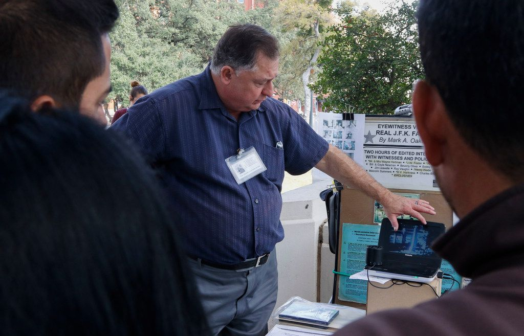 Mark A. Oakes, a J.F.K. assassination researcher, shows a video at his display at Dealey Plaza Tuesday, November, 14, 2017. Oakes has been at Dealey Plaza selling various videos on the President Kennedy assassination since 1995. (Ron Baselice/The Dallas Morning News)