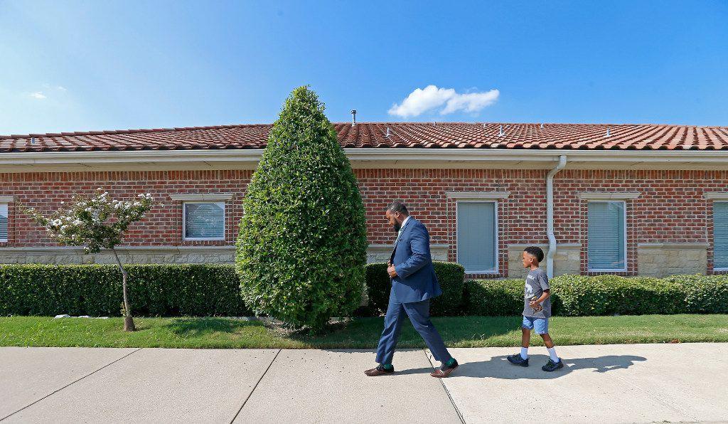 Attorney Lee Merritt (left) and his 7-year-old son Stacy Merritt, Jr., walks to the North Texas Orthodontic Associates' office in Allen.