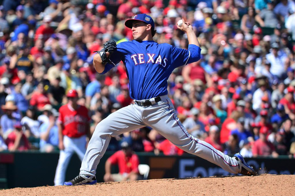 TEMPE, AZ - MARCH 13:  Derek Holland #45 of the Texas Rangers delivers a pitch in the second inning against the Los Angeles Angels during the spring training game at Tempe Diablo Stadium on March 13, 2016 in Tempe, Arizona.