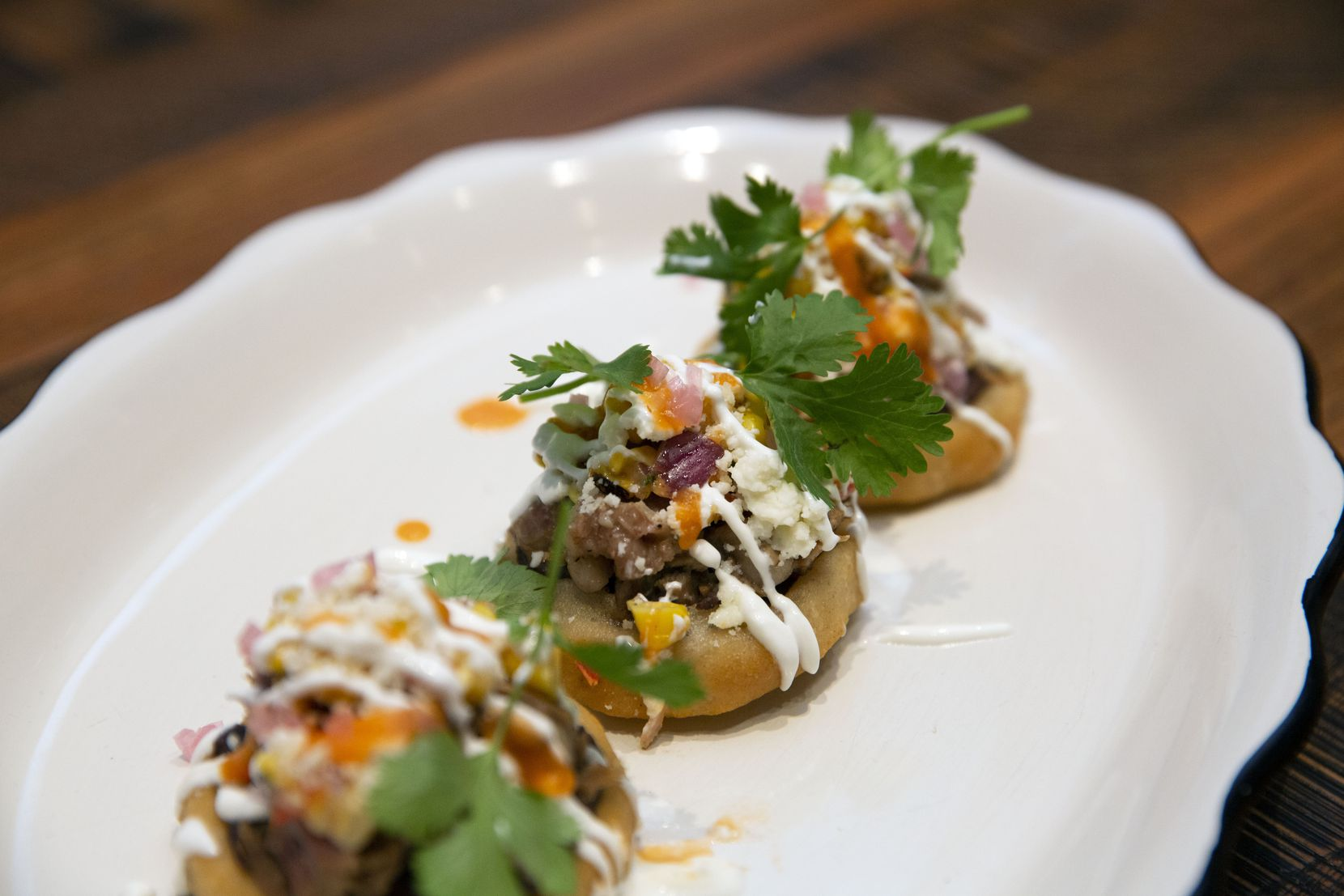 Sopes are given a Texas spin with a filling of smoked brisket, black beans, lime crema, charred corn relish, queso fresco and habanero salsa,