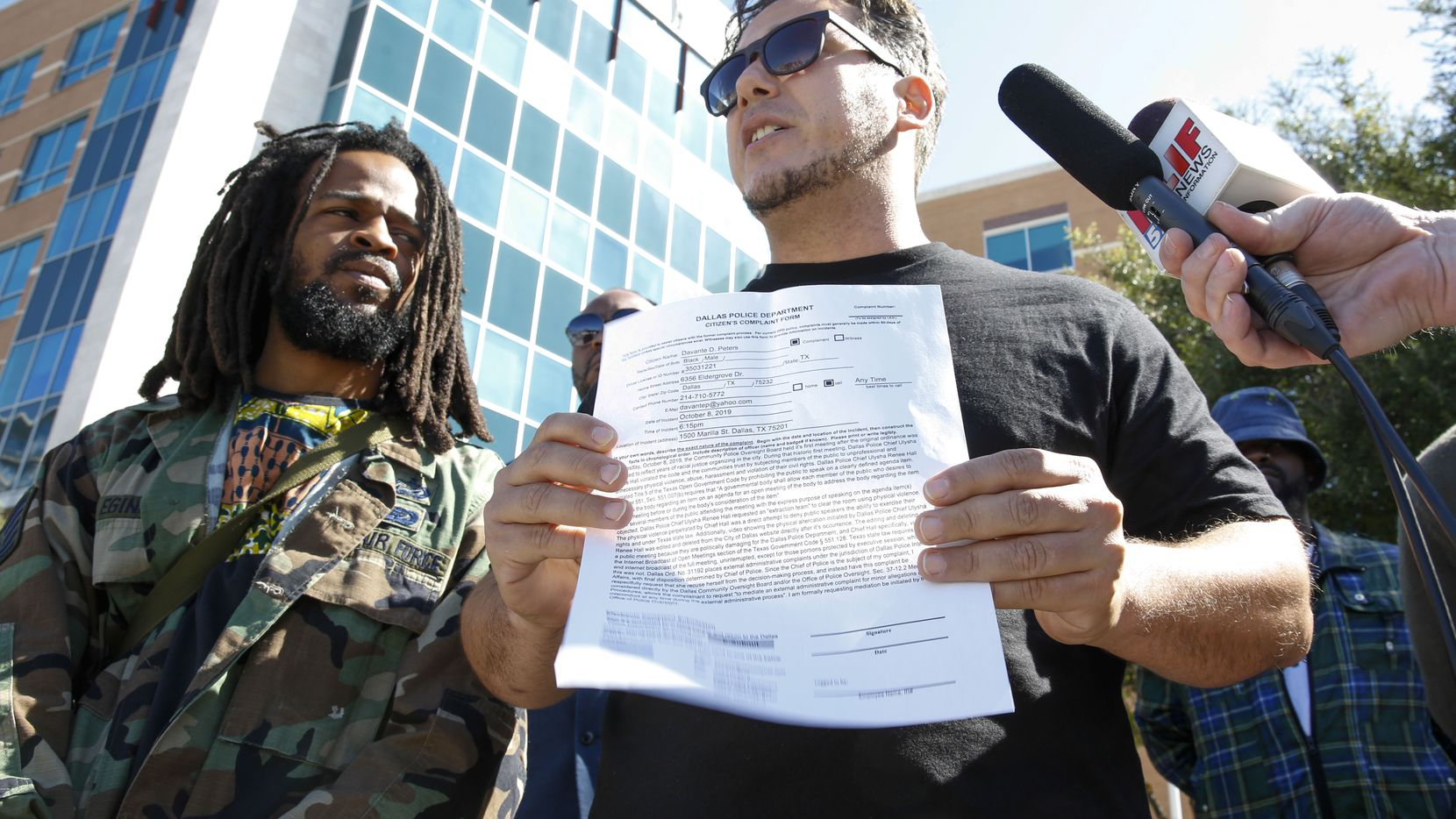 Stephen Benavides from Dallas Communities Organizing for Change holds up an official complaint against Dallas Police Chief U. Reneé Hall  with Davante D. Peters of Community Engagement Specialist (Brian Elledge/Staff Photographer)