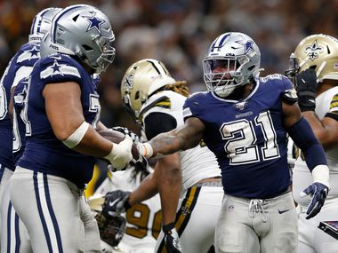 FILE - Cowboys running back Ezekiel Elliott (21) hands the ball to offensive tackle La'el Collins (71) after scoring a touchdown in the second half of a game against the Saints at the Superdome in New Orleans on Sunday, Sept. 29, 2019.