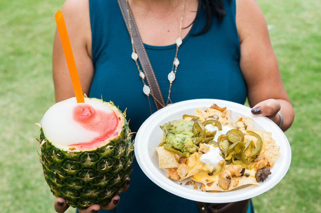 A festivalgoer shows her nachos and pineapple drink at the 2017 Taste Addison.