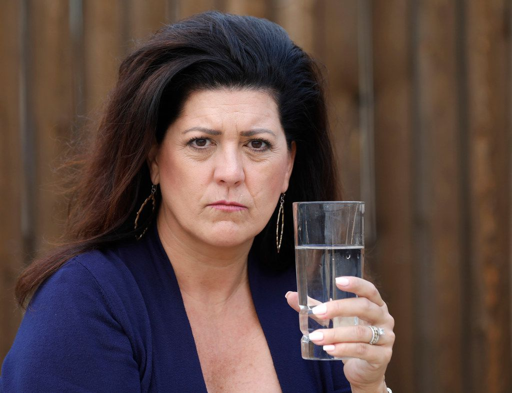 McKinney resident Kelly Broussard poses for a portrait with tap water at her home, Tuesday, April 3, 2018. She and her daughters have experienced itchy, aggravated skin that they fear could be a result of high chlorine levels in their water. She's part of a group on Facebook that organized after environmental activist Erin Brockovich's criticized Plano's water on Facebook. Brockovich is in town Thursday to talk to local residents and also meet with the North Texas Municipal Water District, which supplies water to Plano and dozens of other cities.