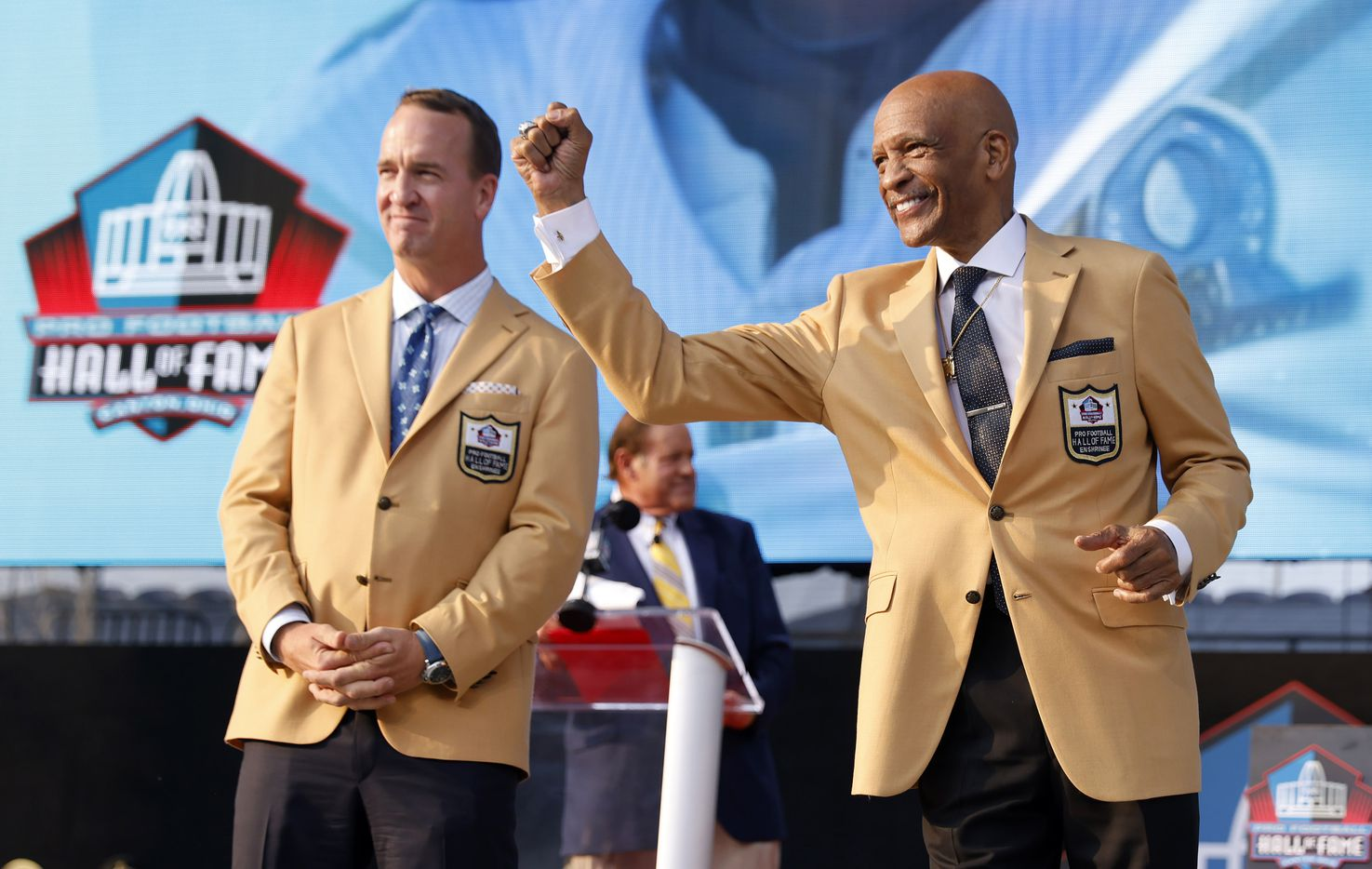 Pro Football Hall of Fame inductee Drew Pearson of the Dallas Cowboys pumps his fist to his friends, family and fans as the Class of 2021 is introduced during the enshrinement ceremony at Tom Benson Hall of Fame Stadium in Canton, Ohio, Sunday, August 8, 2021. Peyton Manning of the Indianapolis Colts is pictured on the right. (Tom Fox/The Dallas Morning News)