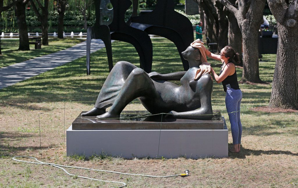 The grass around sculptor Henry Moore's Reclining Figure looks mostly dead as Nicole Berastequi of the Nasher Sculpture Center cleans the work on Aug. 17, 2018.