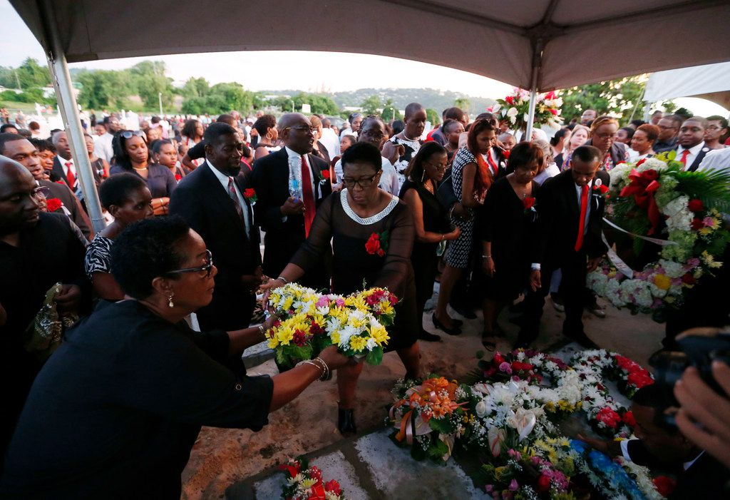 Allison Jean places flowers on the gravesite of her son Botham Shem Jean at Choc Cemetery in Castries, St. Lucia on Monday, September 24, 2018. Jean was shot and killed in his apartment by off duty Dallas police officer Amber Guyger. (Vernon Bryant/The Dallas Morning News)