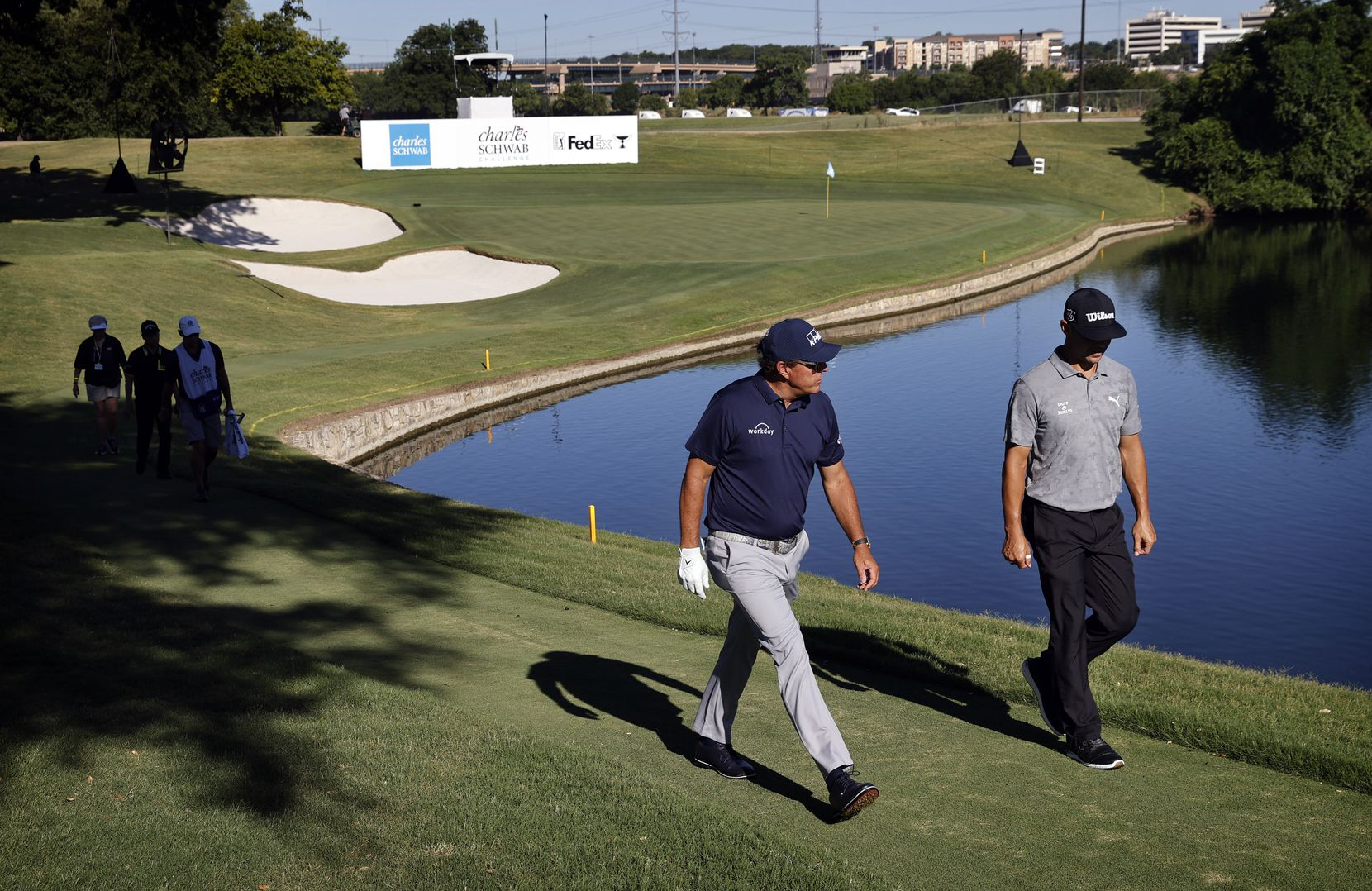 After finishing the par-3 No. 13, PGA Tour golfers Gary Woodland (right) and Phil Mickelson walk to the 14th tee box during the opening round of the Charles Schwab Challenge at Colonial Country Club in Fort Worth on Thursday, June 11, 2020.