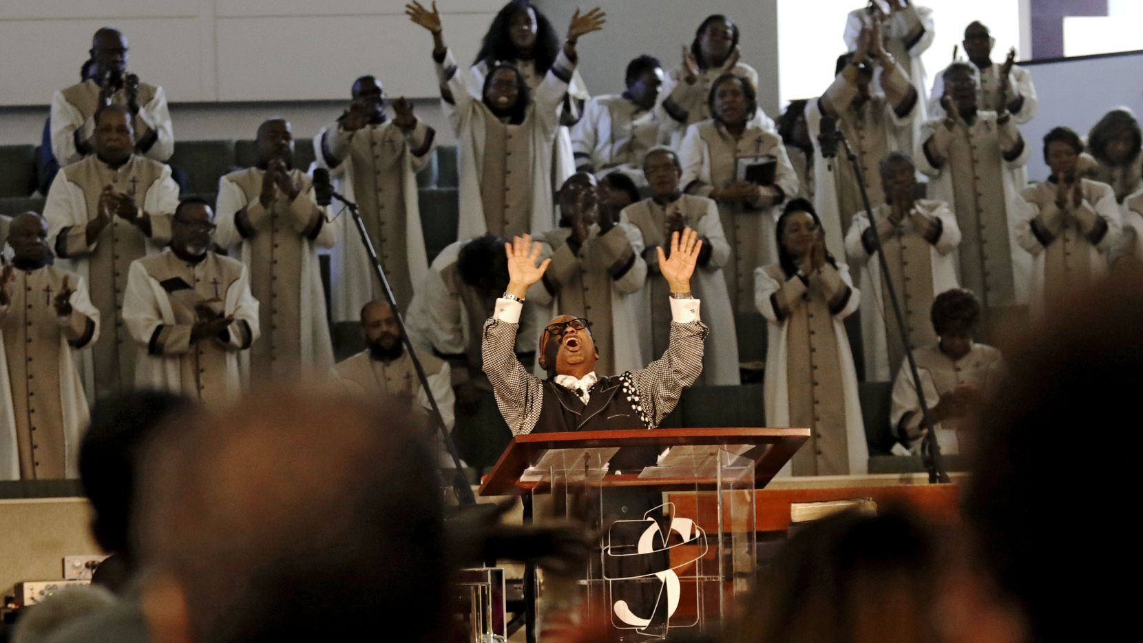 Pastor Isiah Joshua lifts his hands heavenward while preaching at Shiloh Missionary Baptist Church in Plano.