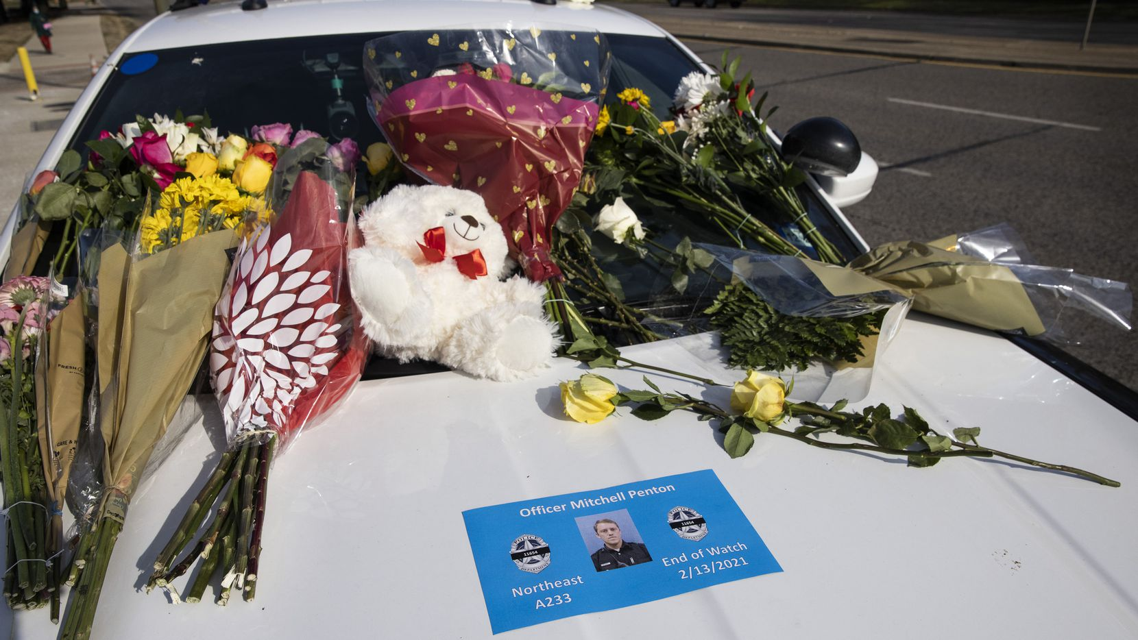 Flowers covered the windshield of a Dallas police car as people paid their respects to fallen Officer Mitchell Penton at the Northeast Patrol Division building on Saturday.