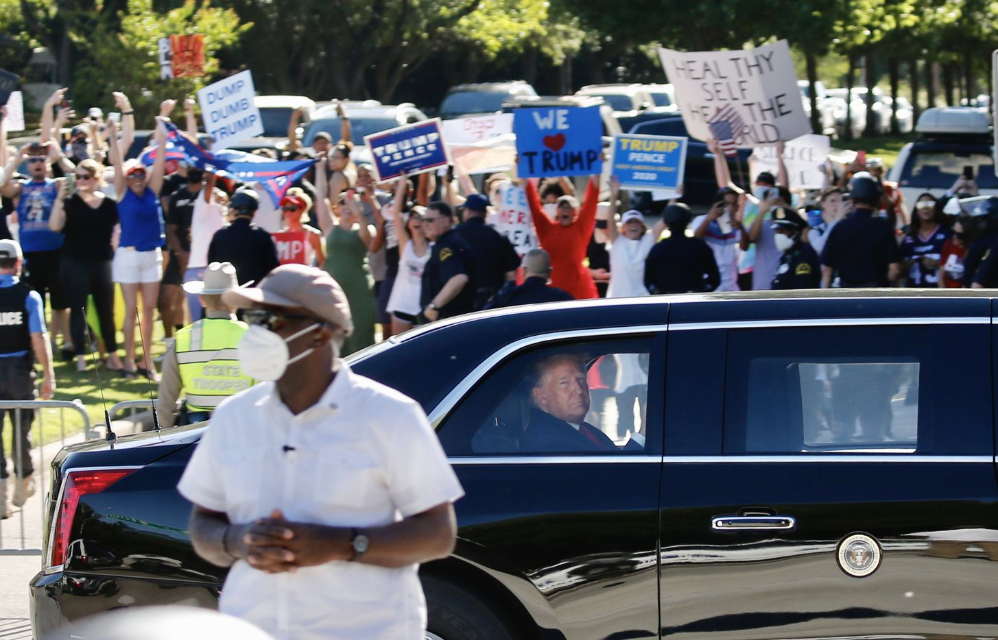 "Supporters and detractors line the road as President Donald Trump rides in ""The Beast,"" the Presidential limo, on Hillcrest after leaving Gateway Church in Dallas, on Thursday, June 11, 2020. President Trump is in town for multiple events. (Vernon Bryant/The Dallas Morning News)"