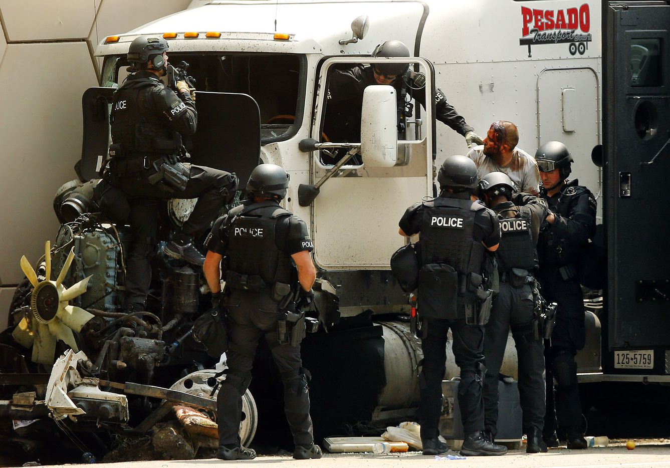 SWAT team members pull a man from a wrecked semi truck after it crashed following a high speed chase on eastbound Interstate 30 at Cooper St. in Arlington  Friday, June 9, 2017. The standoff lasted until police talked the injured man into coming out. (Tom Fox/The Dallas Morning News)