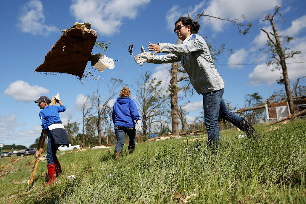 Sarah Jones, an Emory ISD teacher, helps to clean up debris along US-69 after a tornado impacted Emory, Texas on Sunday April 30, 2017. Tornadoes whipped through Van Zandt, Henderson and Rains counties Saturday evening with reports of multiple deaths and dozens injured.