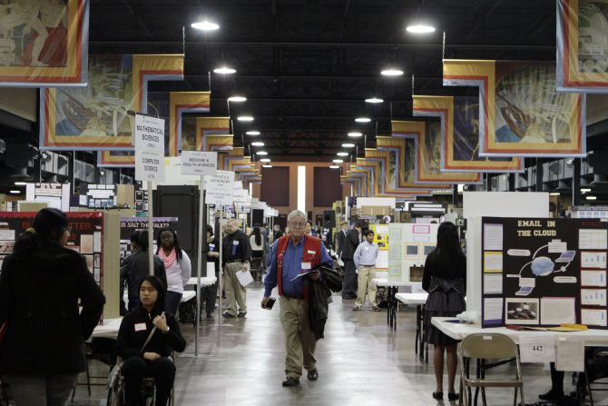 Gary Seidel, a judge representing Frontiers of Flight Museum, walks through the hall displaying high school student projects at this year's 2014 Dallas Regional Science and Engineering Fair.