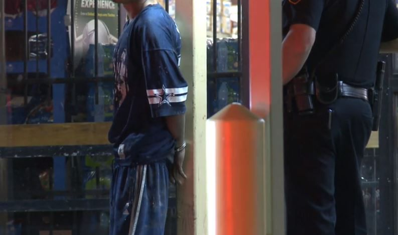 A suspect in the burglary of a grocery store waits in handcuffs as Fort Worth police search the area Wednesday morning.