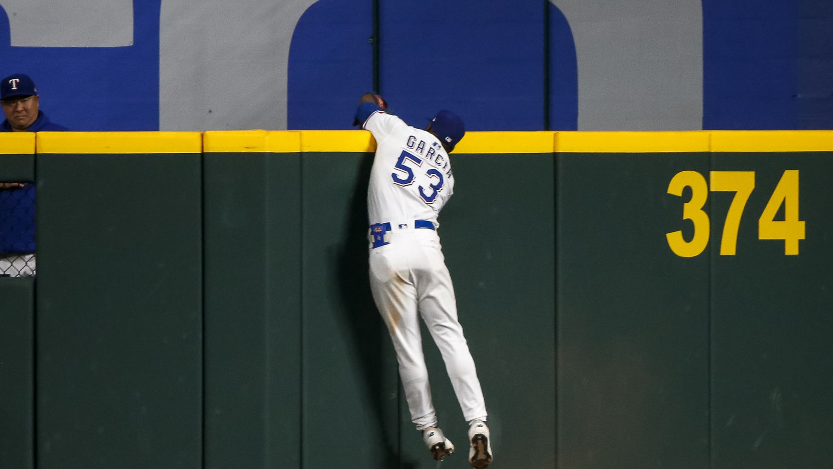 Texas Rangers right fielder Adolis Garcia (53) makes a leaping catch over the outfield wall to steal a home run from Seattle Mariners center fielder Jake Fraley (28) during the eleventh inning at Globe Life Field on Thursday, Aug. 19, 2021, in Arlington.