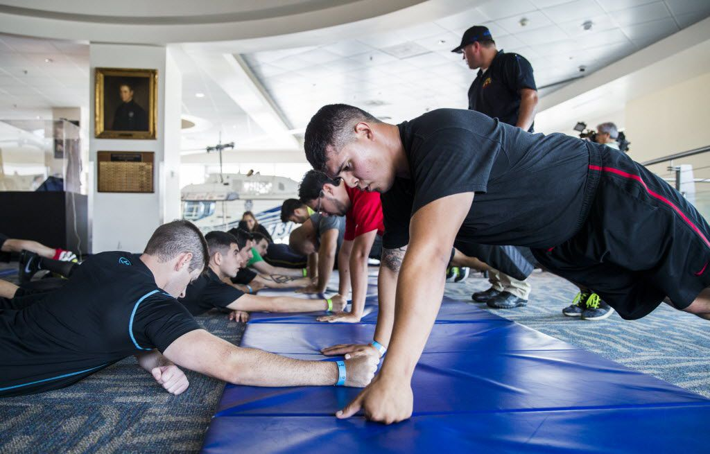 Dallas police applicants Ross Harbor (left) and Tony Hinojosa (right)  do pushups while undergoing physical tests on August 18, 2016 at police headquarters in Dallas.   (Ashley Landis/The Dallas Morning News)