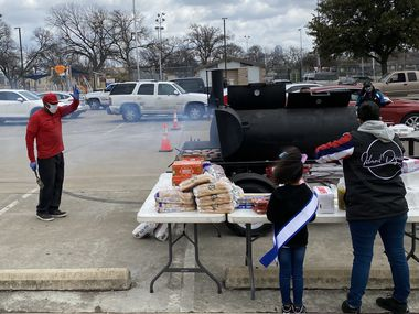 Tyrone Acy, 43, waves to volunteers at the water distribution site in West Dallas as he prepares burgers and hot dogs for families in need. Acy and his wife Erika own Mama 30's Off The Bone BBQ and were able to serve 300 hot meals Sunday.