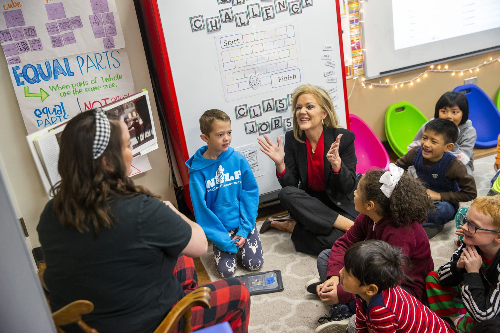 """Richardson ISD Superintendent Jeannie Stone (center) with students during a reading of """"The Polar Express"""" in Kelly Kollaja's second-grade classroom at Wallace Elementary School. Stone has been superintendent of the district for three years, and the RISD board aims to keep her by offering her longevity bonuses the longer she stays in the district."""