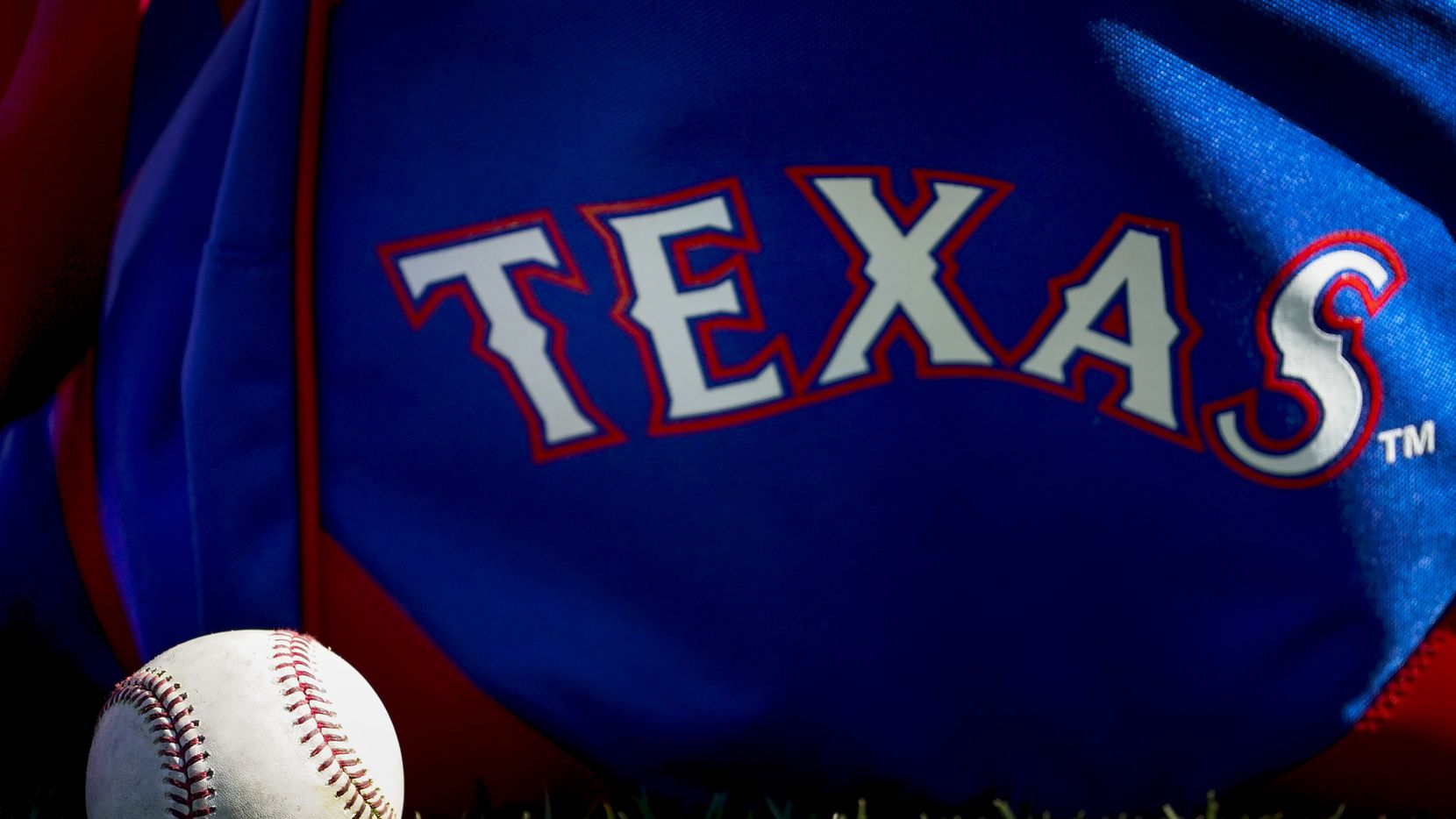 A baseball rests next to a playerÕs bag during a Texas Rangers spring training workout at the team's training facility on Thursday, Feb. 20, 2020, in Surprise, Ariz.