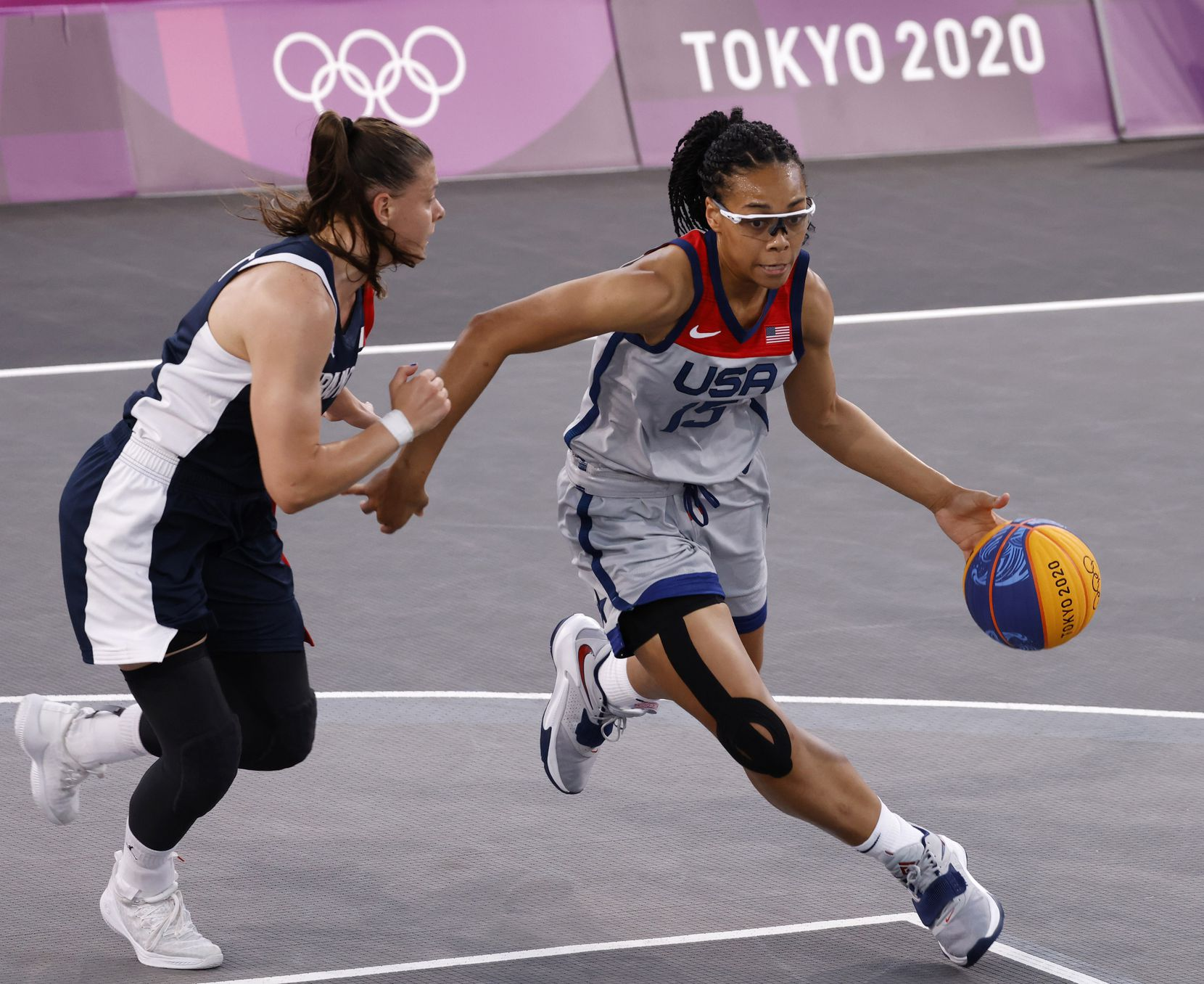 USA's Allisha Gray (15) drives towards the basket as France's Marie-Eve Paget (5) defends during a 3x3 women's basketball game during the postponed 2020 Tokyo Olympics at Aomi Urban Sports Park on Saturday, July 24, 2021, in Tokyo, Japan. USA defeated France 17-10 in the game. (Vernon Bryant/The Dallas Morning News)