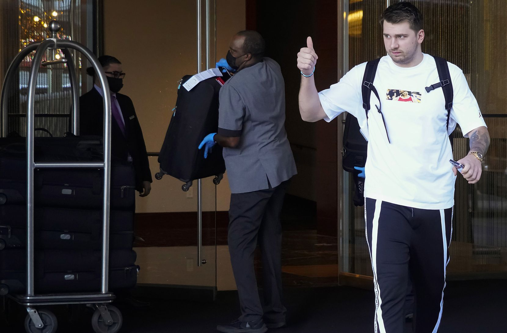 Dallas Mavericks guard Luka Doncic gives a thumbs up to fans as the team leaves their hotel before Game 7 of an NBA playoff basketball series against the LA Clippers at the Staples Center on Sunday, June 6, 2021, in Los Angeles.