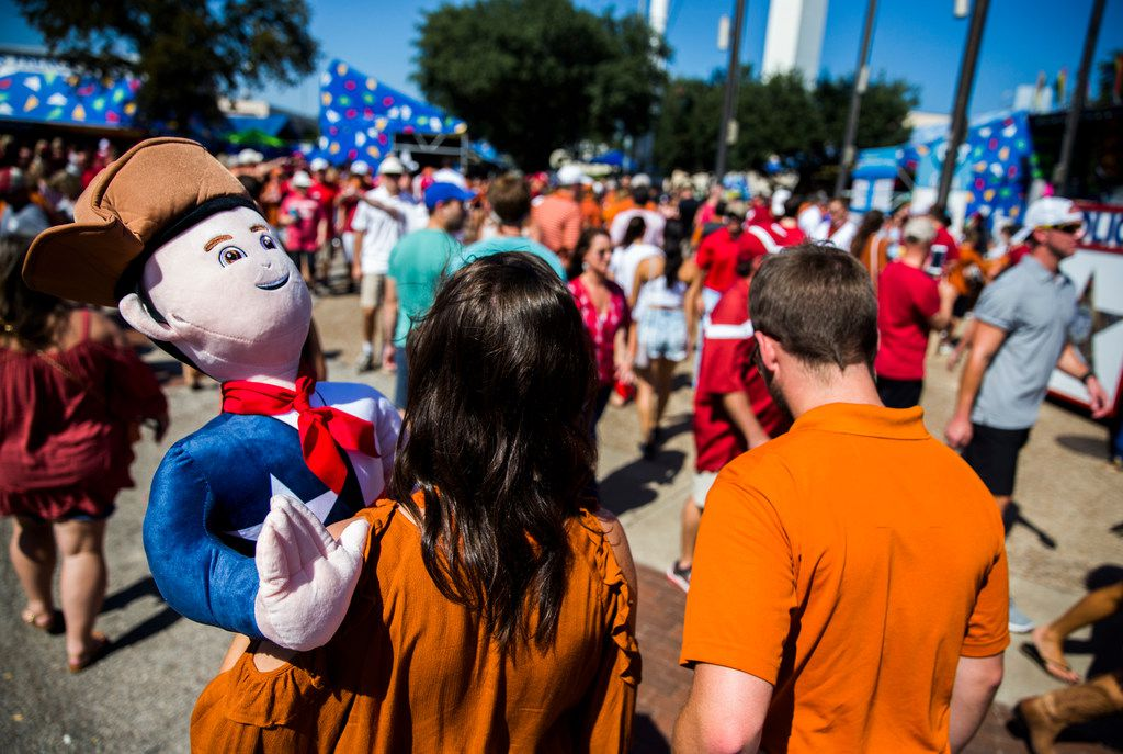 Texas student Kelley Peterson of El Campo, Texas carries a stuffed Little Tex through the Midway with Texas State University student Quinn Dusek, right, before the AT&T Red River Showdown college football game between the University of Texas and Oklahoma University on Saturday, October 14, 2017 at the Cotton Bowl in Fair Park in Dallas. (Ashley Landis/The Dallas Morning News)