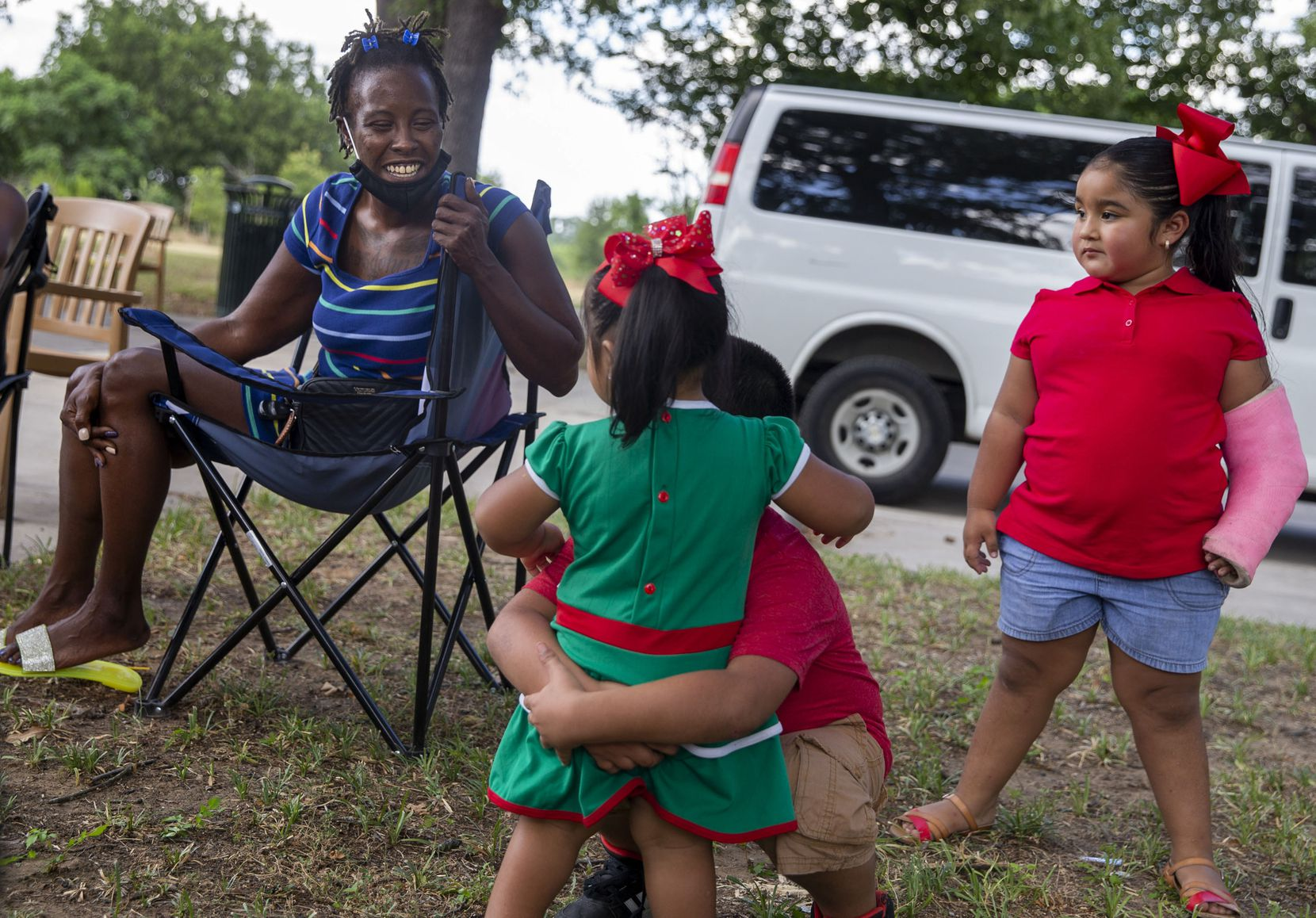 Treewana Davis (left) chats with siblings Yamilet Gonzalez, 2, Isaac Flores, 6, and Janessa Gonzalez, 4, during the Juneteenth celebration at Joppa Park in the Joppa neighborhood on June 19, 2020.