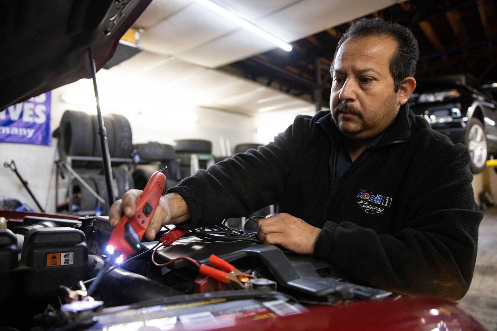 Joaquin Godinez services a car at his auto repair shop in southeast Dallas. He now has Temporary Protected Status and wants permanent immigration status for many reasons, including increasing his ability to secure bank loans that will build his business.