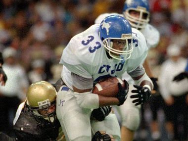 John Tyler High School fullback Marc Broyles drags a pair of Plano East High School defenders for extra yardage during Nov. 26, 1994 playoff game at Texas Stadium. (Tyler Morning Telegraph, file)
