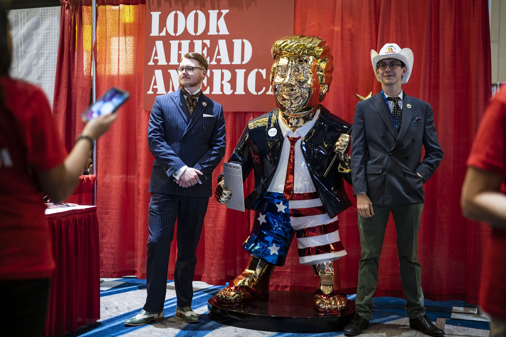 Attendees at the Conservative Political Action Conference in Orlando posed with a golden statue of former President Donald Trump on Feb. 26, 2021. (Jabin Botsford/The Washington Post)
