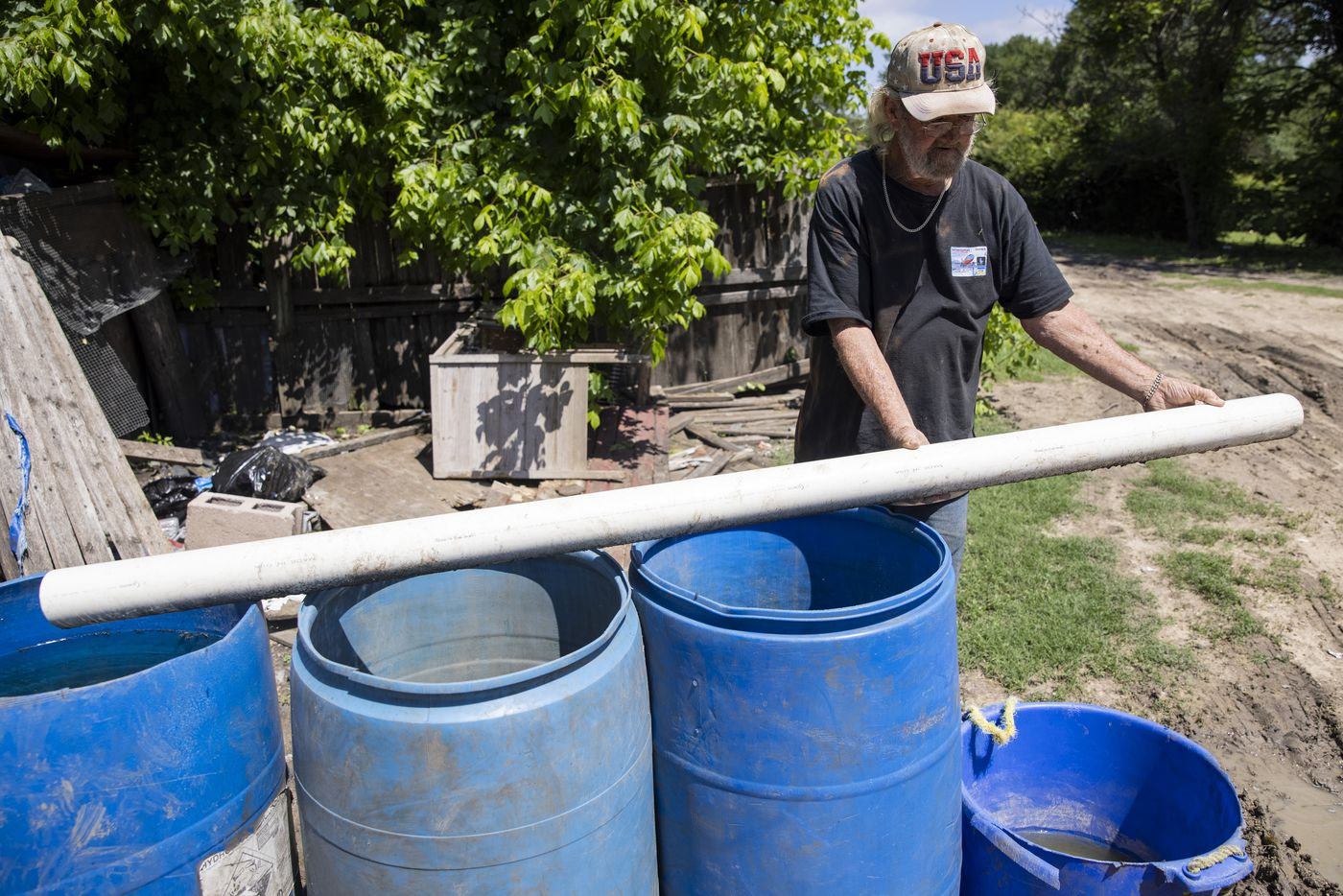 Richard Shivers shows the tube he uses to fill barrels with water from a water container tank he uses to transport water to the lot he shares with Rachel Garcia on Wednesday, May 26, 2021, in Sandbranch. (Juan Figueroa/The Dallas Morning News)